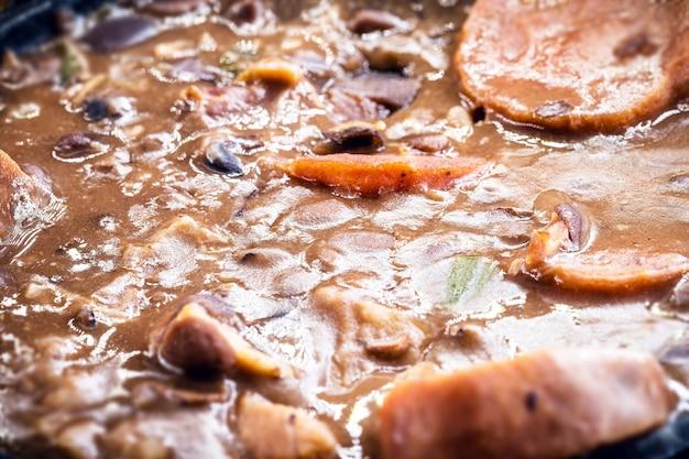 Schweinefleisch mit bohnen, wurst, kohl und pfeffer