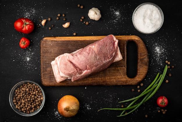 Schweinefleisch mit gewürzen auf schwarzem hintergrund.