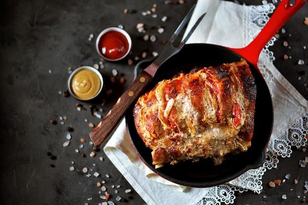 Schweinefleisch mit zwiebeln und tomaten in einer gusseisernen pfanne gebacken.