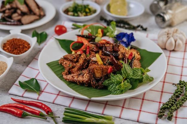 Schweinefleisch nam tok mit gebratenem chili, tomate, limette, gurke und frischem pfeffer. thai essen.
