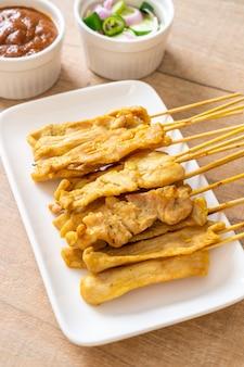 Schweinefleisch-satay - gegrilltes schweinefleisch, serviert mit erdnusssauce oder süß-saurer sauce - asiatische küche