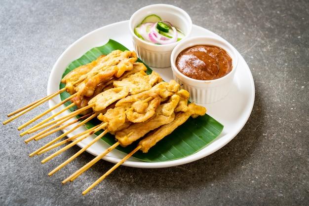 Schweinefleisch-satay - gegrilltes schweinefleisch, serviert mit erdnusssauce oder süß-saurer sauce