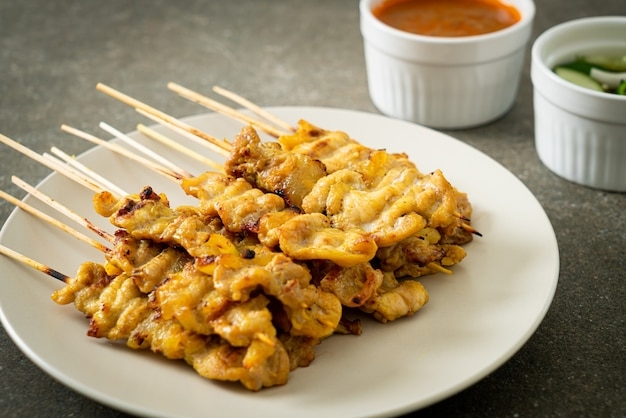 Schweinefleisch-satay mit erdnusssauce gurkenscheiben und zwiebeln in essig - asiatische küche