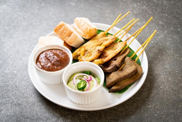 Schweinefleisch-satay mit erdnusssauce und gurken, gurkenscheiben und zwiebeln in essig