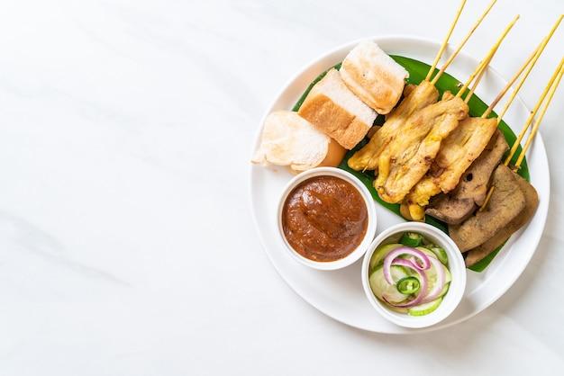 Schweinefleisch satay mit ihrer erdnusssauce und gurken, die gurkenscheiben und zwiebeln in essig sind
