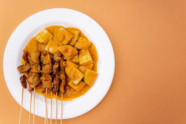 Schweinefleisch-satay oder sate babi schweinefleisch-satay serviert mit einer würzigen padang-sauce und scheiben von lontong- oder ketupat-reiskuchen, garniert mit einer prise bawang goreng knusprig gebratener schalotten