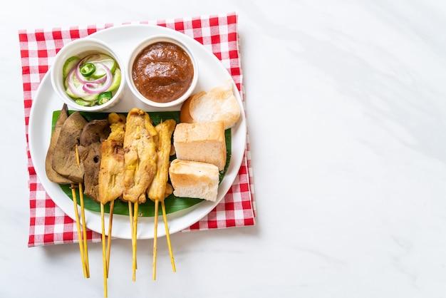 Schweinefleisch-satay und leber-satay mit brot-erdnuss-sauce und gurken, gurkenscheiben und zwiebeln in essig - asiatische küche