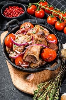 Schweinefleisch shish kebab mit zwiebeln und tomaten in der pfanne. gegrilltes fleisch. schwarzer hintergrund. draufsicht.