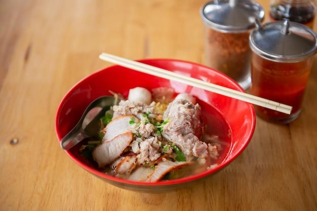 Schweinefleisch tom yum noodle in der roten schüssel, im löffel und in den essstäbchen