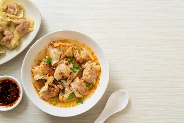 Schweinefleisch-wonton-suppe oder schweinefleischknödelsuppe mit geröstetem chili - asiatische küche