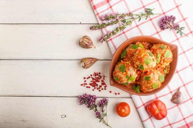 Schweinefleischbällchen mit tomatensauce, oreganoblättern, gewürzen und kräutern in tonschale mit leinentextil. ansicht von oben