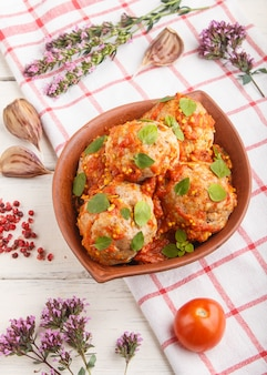 Schweinefleischbällchen mit tomatensauce, oreganoblättern, gewürzen und kräutern in tonschale mit leinentextil. seitenansicht