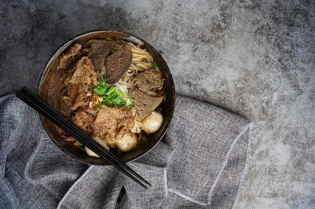 Schweinefleischbootnudeln, klassisches thailändisches essen und beliebte menüs sowie verzehrfertige suppen. es gibt auch ein basilikum in der schüssel.