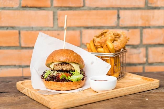 Schweinefleischburger mit zwiebelringen und pommes frites