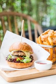 Schweinefleischburger mit zwiebelringen und pommes-frites