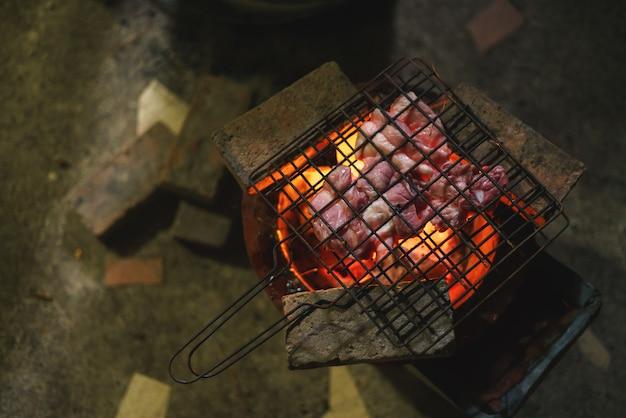 Schweinefleischgrill über gebrannter glühender holzkohle