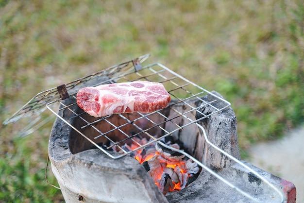 Schweinefleischgrill über verbrannter glühender holzkohle