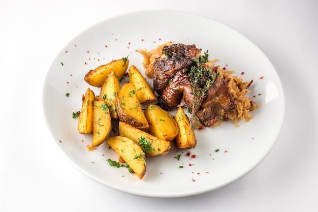 Schweinefleischknöchel mit kartoffeln und kohl auf einer weißen platte
