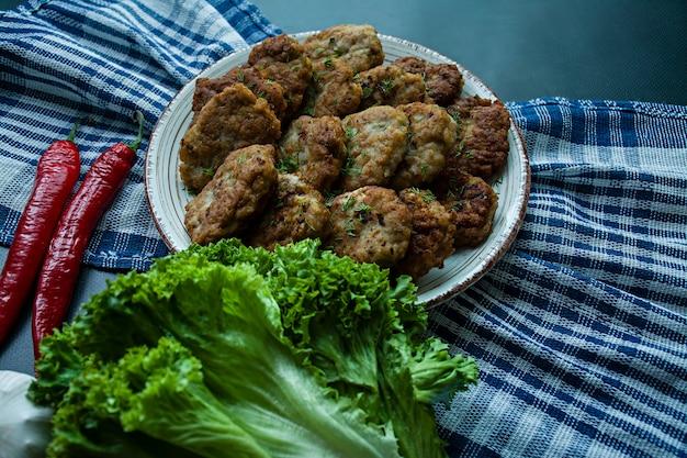 Schweinefleischkoteletts auf einer platte mit grüns und gemüse