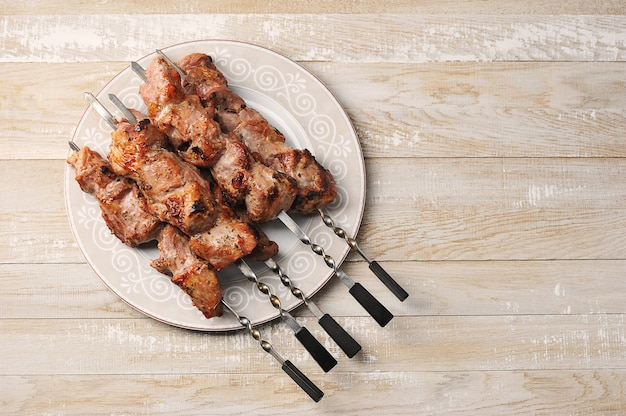 Schweinefleischspieße auf spieße in einer platte auf einem hölzernen hintergrund
