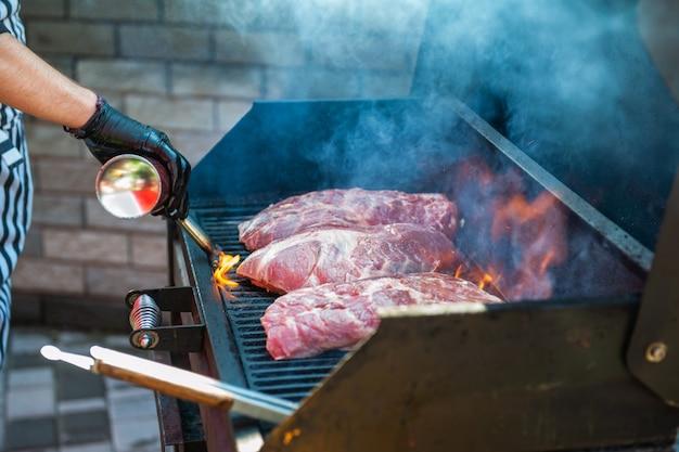 Schweinefleischsteaks auf dem grill mit flammen