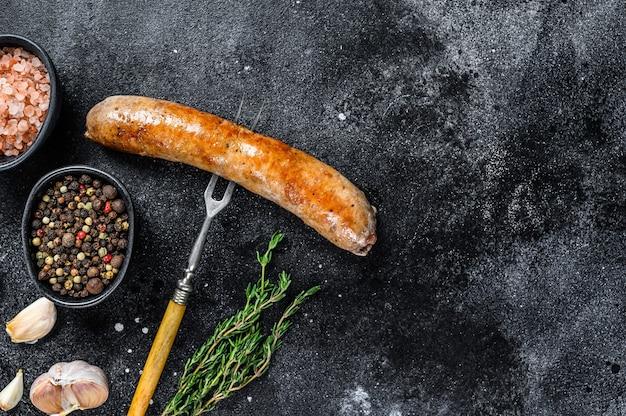 Schweinefleischwurst bbg mit gewürzen und kräutern auf einer fleischgabel gegrillt