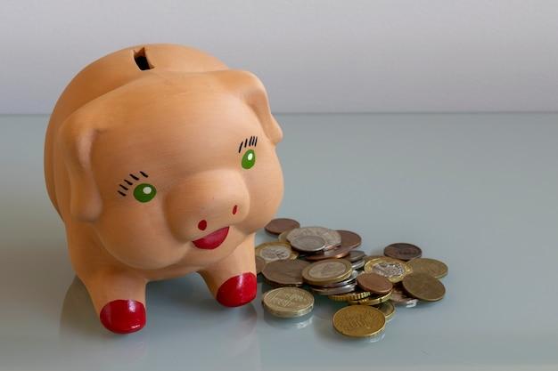 Schweineförmiges sparschwein mit münzen auf dem seitenwirtschaftskonzept