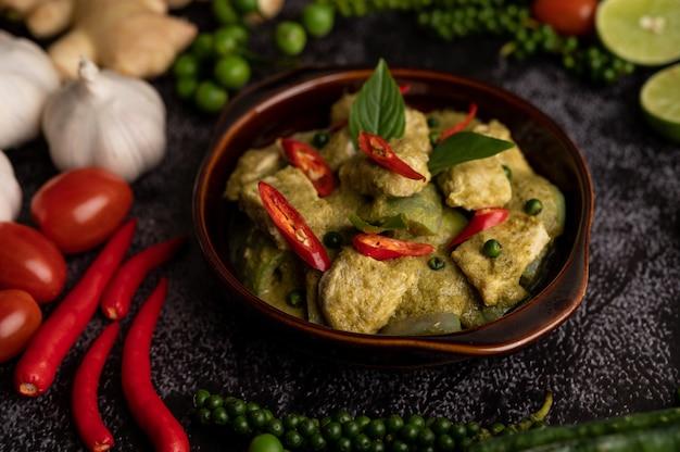 Schweinegrünes curry in einer braunen schüssel mit gewürzen auf einem schwarzen zementhintergrund