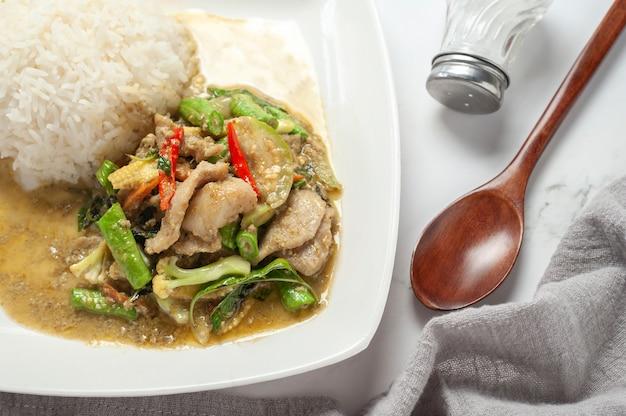 Schweinegrünes curry mit gekochtem reis. draufsicht.
