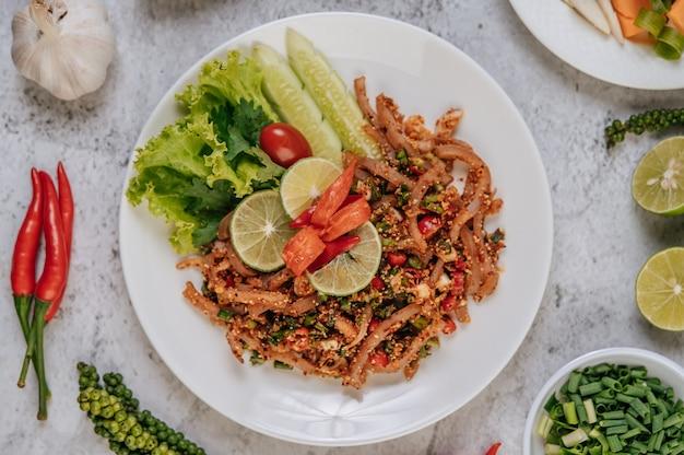Schweinehaut larb mit karotten, gurken, limetten, frühlingszwiebeln, chili, frisch gemahlenem pfeffer und salat.