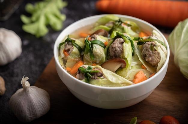 Schweinekohlsuppe mit karotten, gehackten frühlingszwiebeln, gurke in einem holzteller auf einem holzteller