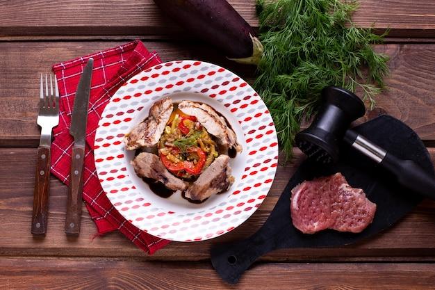 Schweinekotelett mit geröstetem gemüse auf dem tisch
