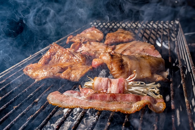Schweinekotelett und speck eingewickeltes enoki, gegrillt auf holzkohlegrill, asiatische kochkultur