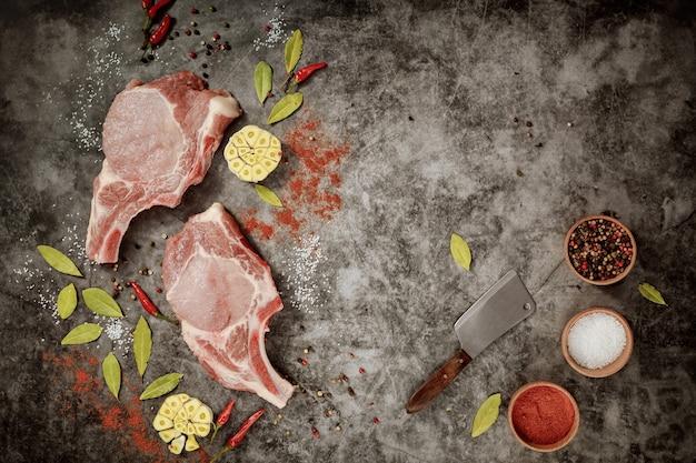 Schweinekoteletts mit rippchen, hackmesser und gewürzen. draufsicht.