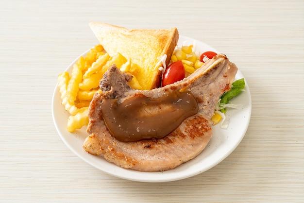 Schweinekotelettsteak mit pommes und minisalat auf weißem teller