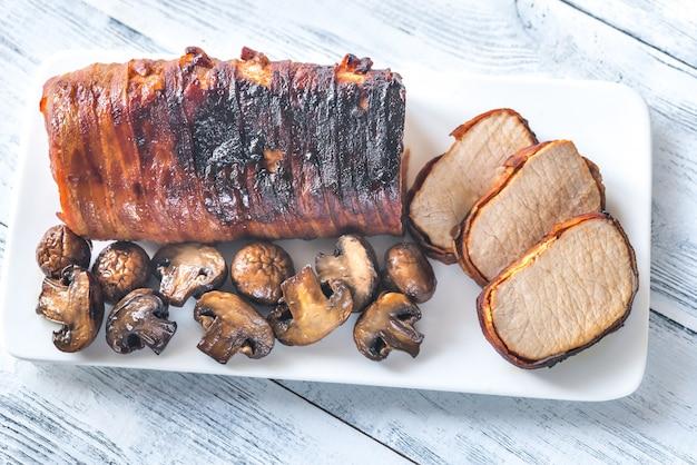 Schweinelende in speck mit gerösteten pilzen gewickelt