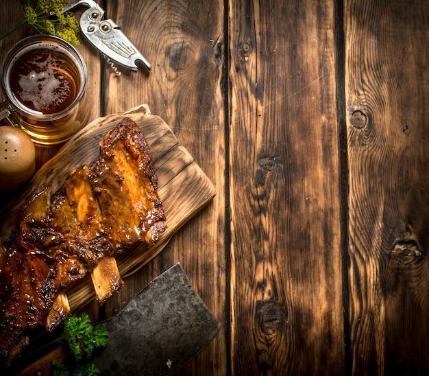 Schweinerippchen gegrillt mit einem fleischbeil und bier auf holztisch.