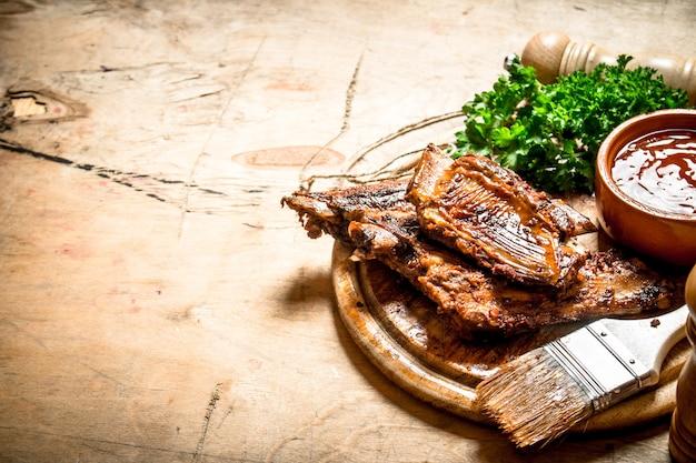 Schweinerippchen gegrillt mit einer würzigen sauce und einem pinsel auf holzhintergrund