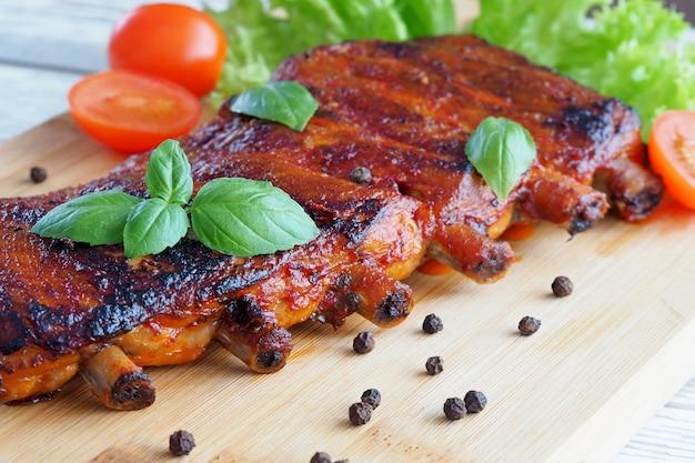 Schweinerippchen in tomaten-bbq-sauce mit basilikumblättern auf schneidebrett