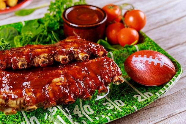 Schweinerippchen mit barbecue-sauce auf schwarzem steinbrett. draufsicht mit kopierraum