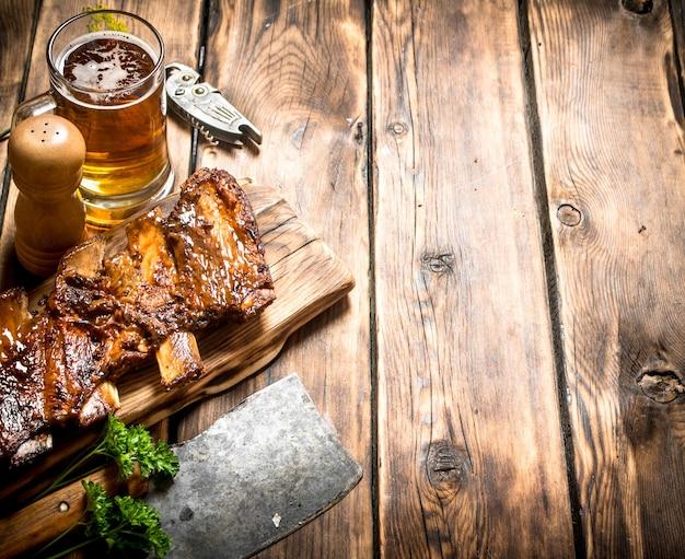 Schweinerippchen mit fleischbeil und bier gegrillt. auf einem holztisch.