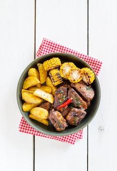 Schweinerippchen mit kartoffeln auf einem holztisch. grill. grill. amerikanische küche. rezept.