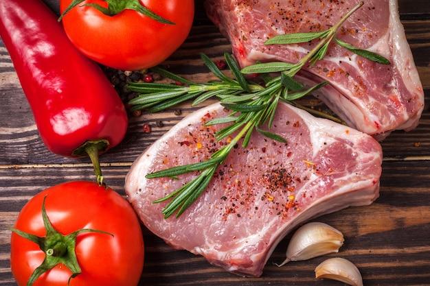 Schweinesteak mit gewürzen und rosmarin. saftiges und frisches rohes fleisch mit gemüse und erbsen auf einem