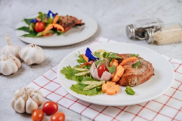 Schweinesteak mit tomaten, karotten, roten zwiebeln, pfefferminze, schmetterlingserbsenblüte und limette.
