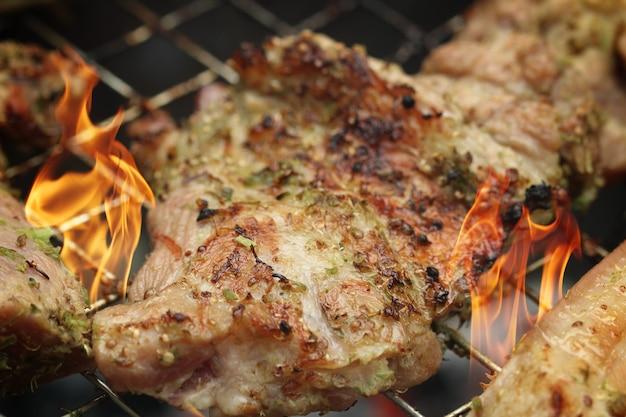 Schweinesteaks auf dem grill mit flammen