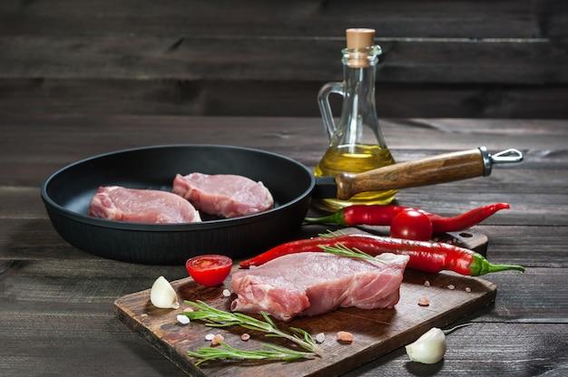 Schweinesteaks auf der pfanne, fertig zum kochen. frisches rohes fleisch, holzoberfläche, selektiver fokus