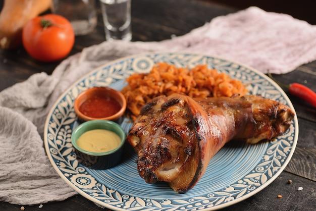 Schweinshaxe mit gedünstetem kohl und soße. auf einem holztisch mit dekor