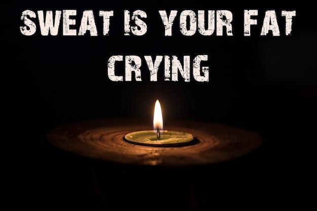 Schweiß ist dein fettes weinen - weiße kerze mit dunklem hintergrund - in einem hölzernen kerzenständer.