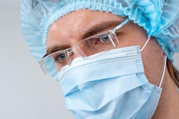 Schweißchirurg in operationsmaske