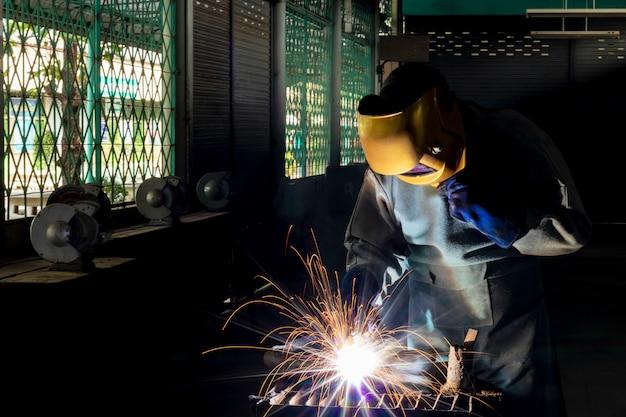 Schweißen mit werkstückstahl. arbeitsschweißerstahl unter verwendung der sicherheitsausrüstung des elektrischen schweißgeräts in der fabrikindustrie.